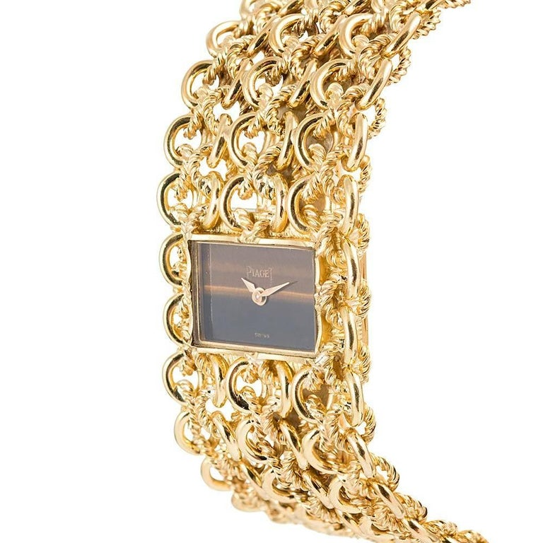 Sophisticated and glamourous, this mid-century treasure nestles a rectangular tiger's eye watch in a woven bracelet of high-polished and matte-finished golden threads. The bracelet is of Piaget manufacture and measures 6.5 by 1 inch. It is finished