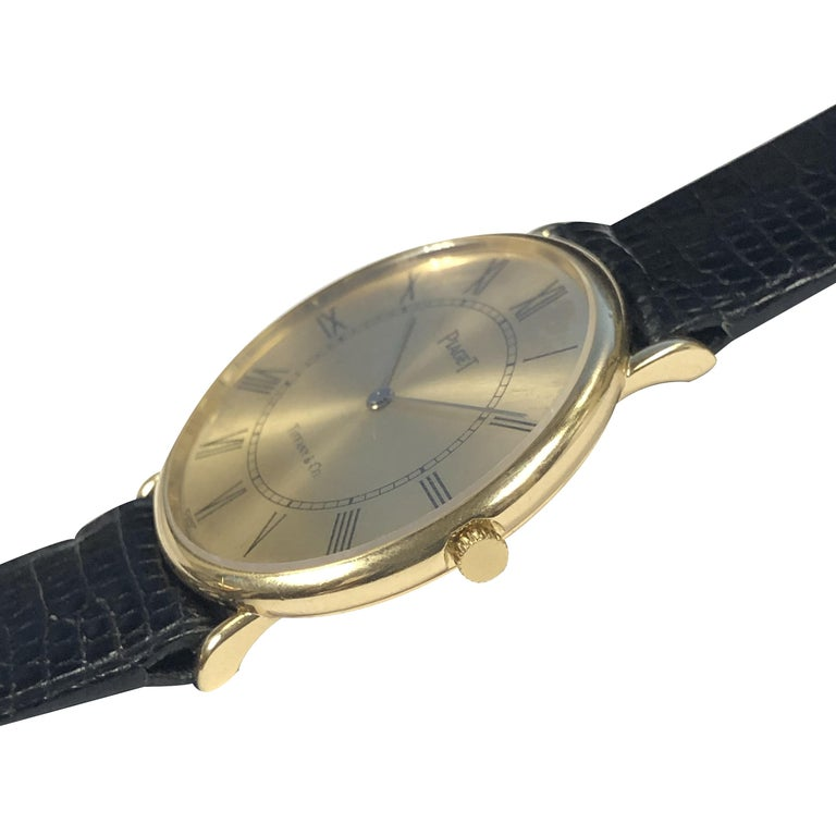 Circa 1980s Piaget Retailed by Tiffany & Company.   30 M.M. Diameter X 4 M.M. thick 18K Yellow Gold 2 piece case, 17 jewel mechanical, manual wind movement., Gold dial with Black Roman  Numerals. New Piaget Black Lizard strap with replaced Gold tone