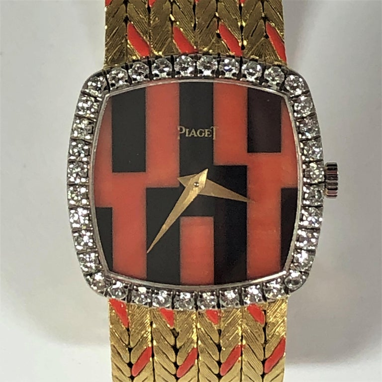 A sophisticated, 18K Yellow Gold cushion shaped ladies Piaget watch with a unique coral and onyx dial, diamond bezel, and band. The integral gold band has coral colored enamel markings to complement the dial. Measuring 7.5 inches long (190mm) by