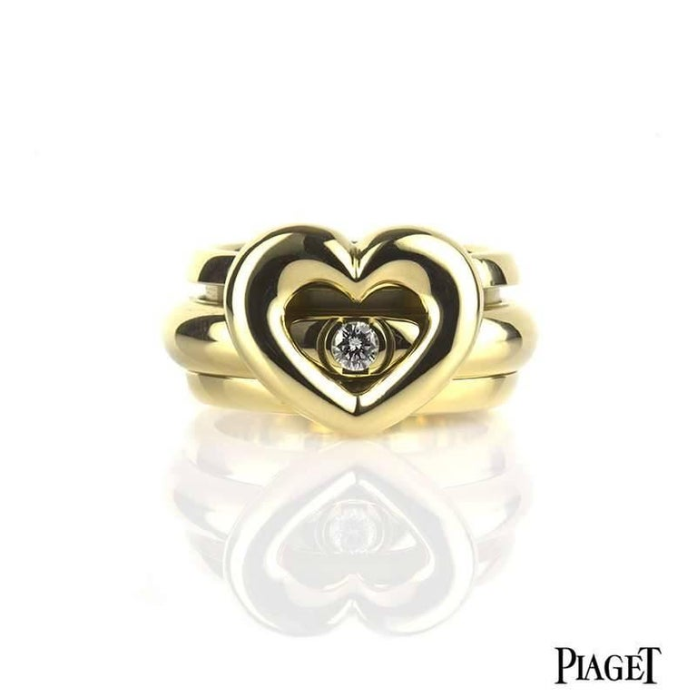 A Piaget Possession ring in 18k yellow gold set with one round brilliant cut diamond. The 0.15ct diamond is set in the inner of the two bands, which move freely around each other in perpetual movement. The open heart motif is set to the front and