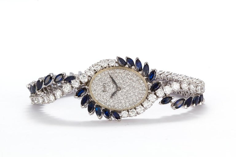 We are pleased to offer this Vintage 1950's Piaget Platinum Diamond & Sapphire Ladies Watch. This stunning watch features a tennis bracelet style design set with and estimated 6.25ctw D-F/VS1-VS2 Round Brilliant Cut Diamonds and 6.00ctw marquee cut