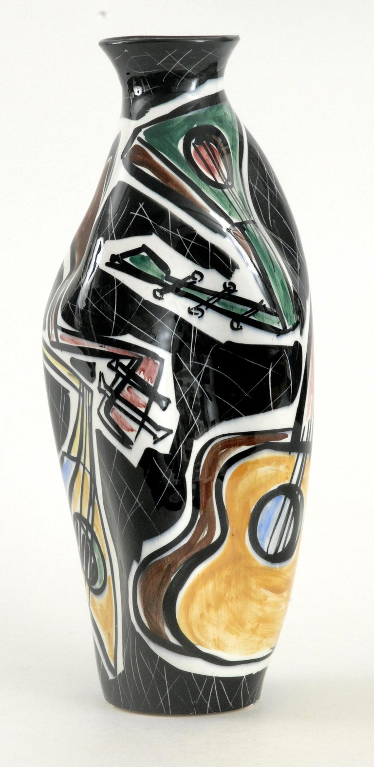 A large highly decorated vase with pushed in sides painted with guitars in various colors and shapes in white cartouches on an overall black background. Stylistically influenced by the Cubist Movement painters, Picasso and Braque et al. Stamped