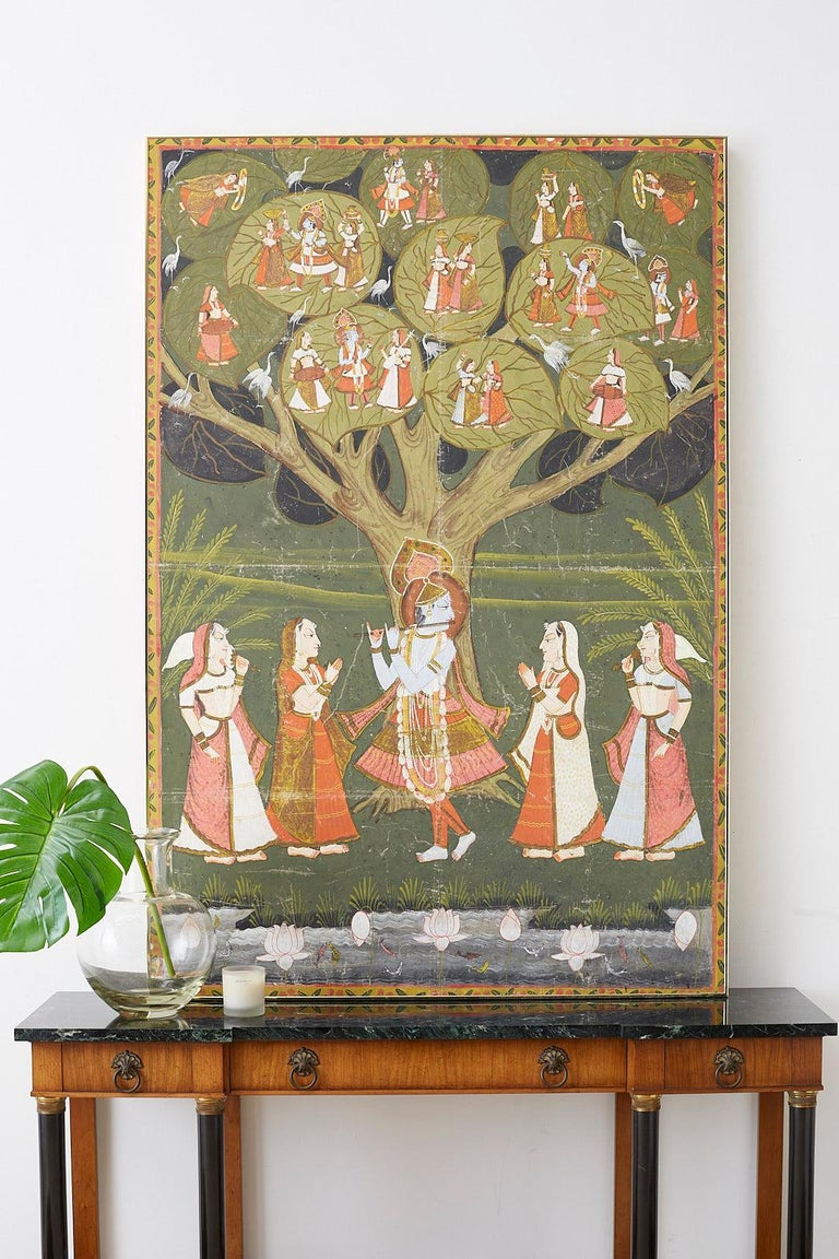 Colorful Pichhwai painting of Hindu deity Krishna depicted under the tree of life. He is playing a basuri flute for gopis of milkmaids. In the tree he is depicted six more times in various scenes with gopis and white cranes watching. Vibrant colors