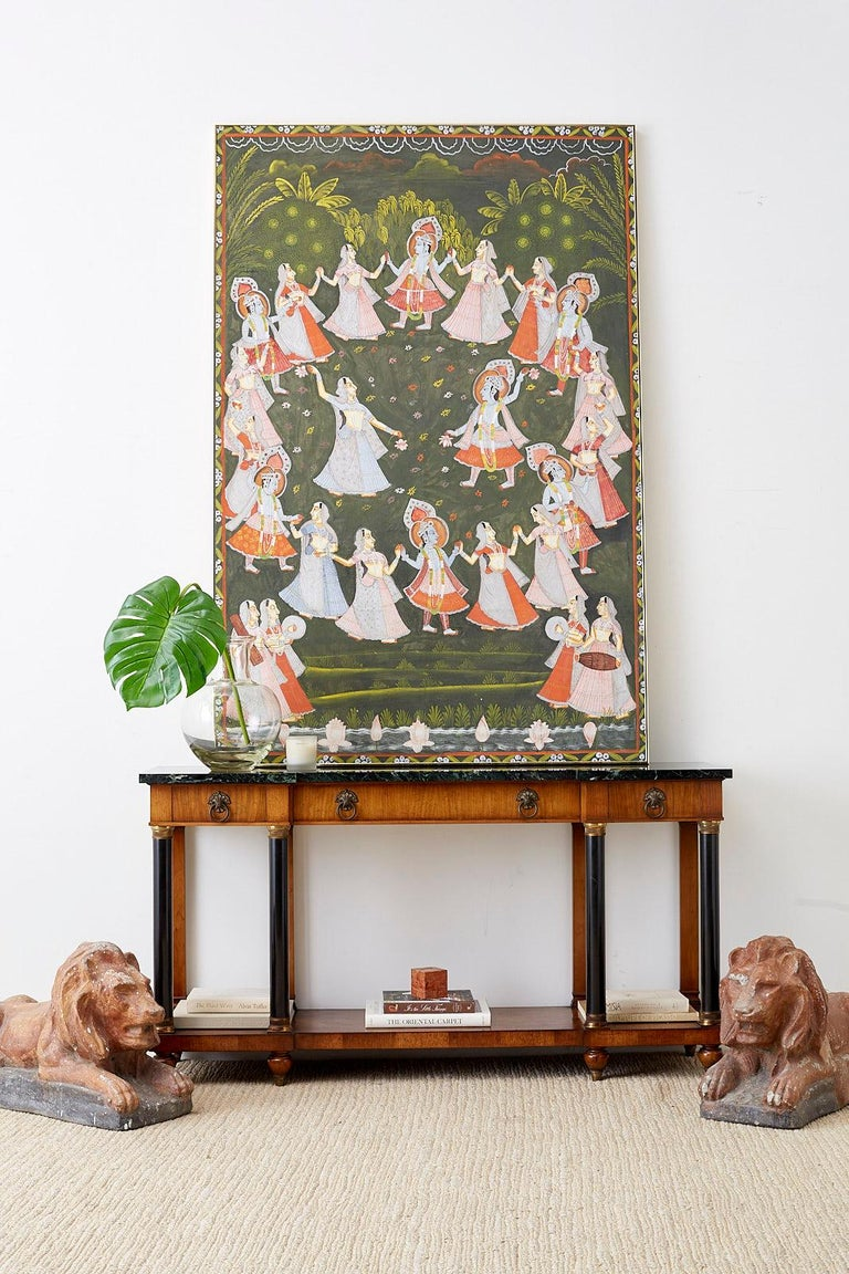 Festive Pichhwai devotional painting of Hindu deity Krishna depicted seven times dancing with pairs of gopis or milkmaids in a circle. This painting features vibrant colors over a green ground. The figures of Krishna are shown adorned in spirited