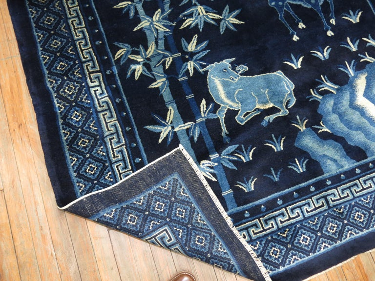 An early 20th century Chinese square rug in predominant shades of midnight blue with a pictorial animal landscaping scene. The wool is very soft and all the colors are natural.
