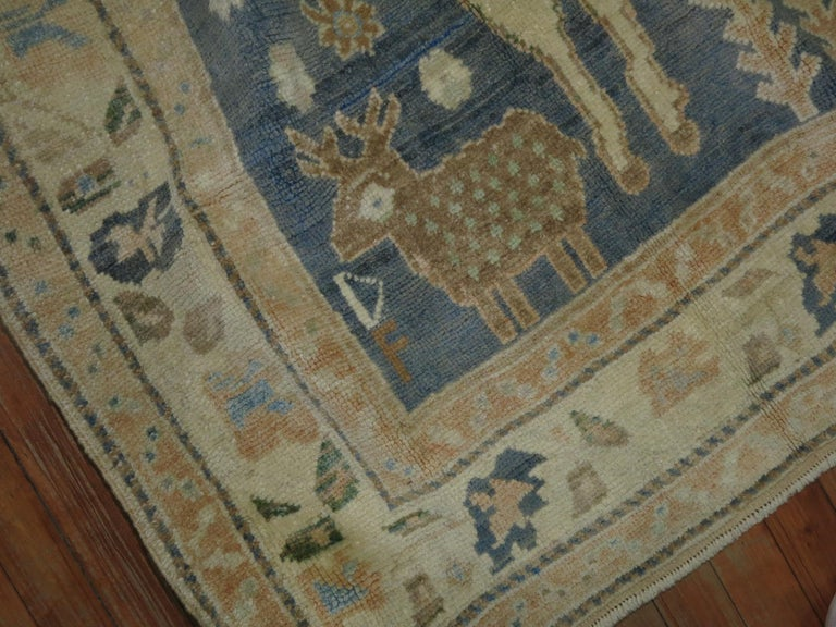 A highly decorative mid-20th century Turkish rug with 2 large sheep on a casual gray blue sea foam colored ground. Smaller birds and sheep hovering around the field too.