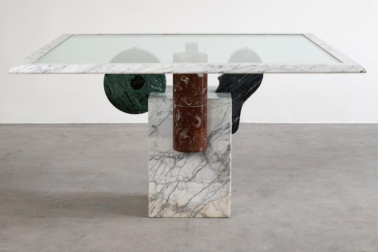 Square table Brugiana with a base in white Carrara marble and geometric elements in arabescato, green alpi, sandstone and red Levanto marble, glass on top with a white Carrara marble frame. Brugiana table was designed by Pier Alessandro Giusti and