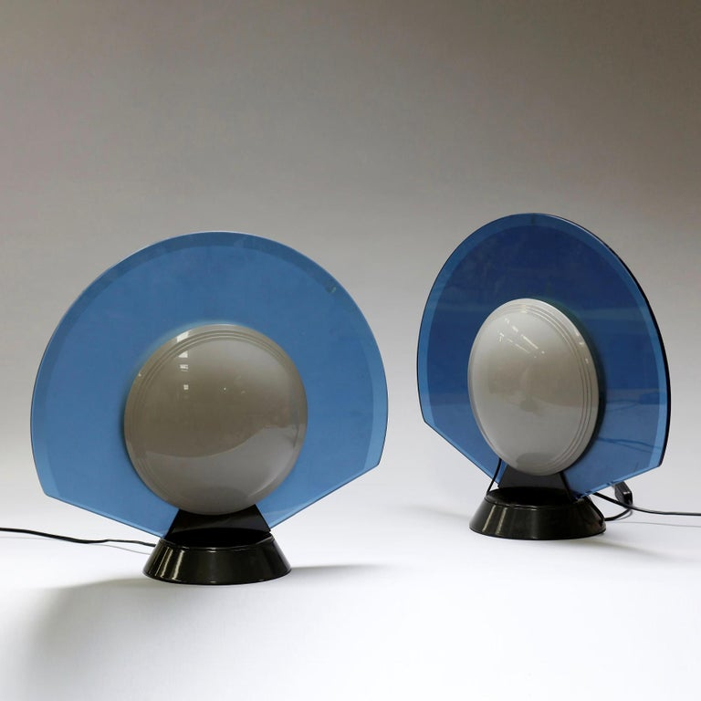 Pier Giuseppe Ramella  Tikal  A pair of table lamps, each with a blue glass half-disc surrounding white half-spherical shades on each side, on a spreading central stem. Produced by Arteluce. Italy, 1982.