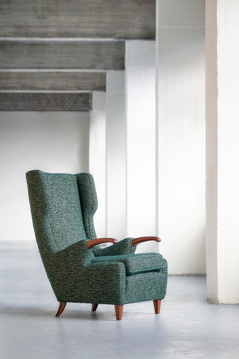 This rare armchair was designed by Pier Luigi Colli and manufactured by his Turin workshop Colli in 1947. The sophisticated design was numbered model 505. The striking curved armrests and legs are in solid walnut. The chair has been fully