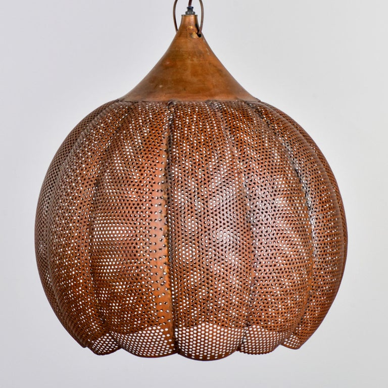 Hanging pendant made of pierced copper in a gourd-like form, circa 1990s. Fixture has one standard sized socket. Found in England. Unknown maker. Wiring has been updated for US electrical standards.
