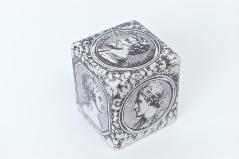 A rare cubic paperweight from the 1950s designed by Piero Fornasetti. This black and white porcelain paperweight is decorated on each side of the cube with the profiles of six Roman heads. Another identical paperweight was seen as part of the family