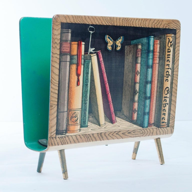 Piero Fornasetti magazine rack with wooden frame and  Hand colored silk-screened decoration. Fornasetti label to the base.  Atelier Fornasetti, Italy, circa 1950.