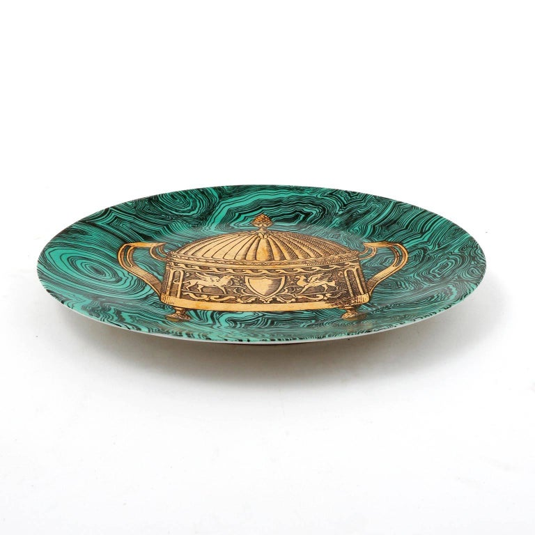 A ceramic or porcelain dish with an emerald green faux malachite ground and painted in gold by Piero Fornasetti, Italy, manufactured in midcentury in 1950s.  This hand-colored decorative plate is one in a series of 'faux malachite' designs that