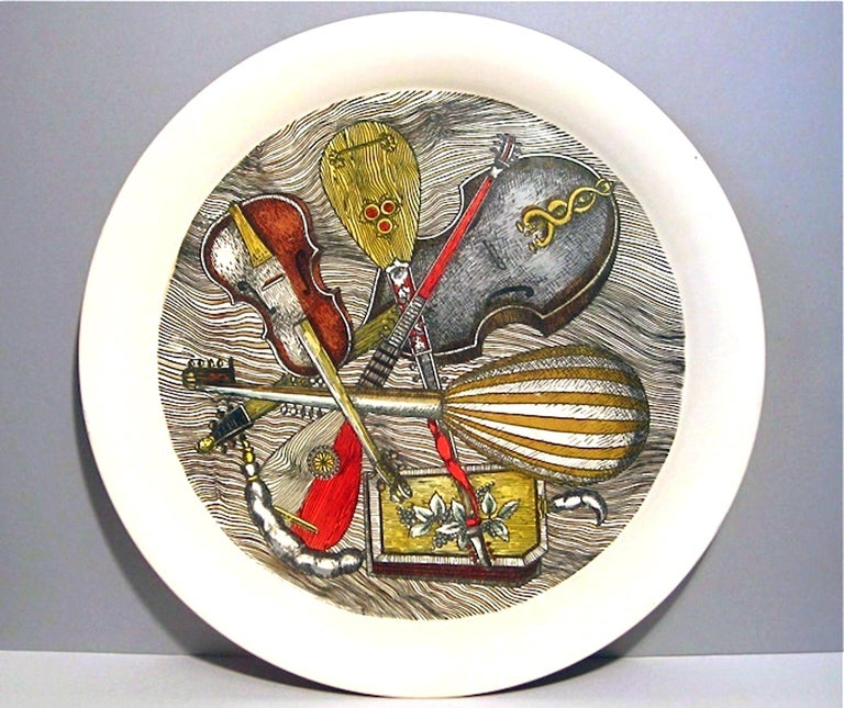 Rare circular tray in Piero Fornasetti's Strumenti pattern with a variety of stringed instruments on a white ground. Typical frits to edge in one place.   Reference: Fornasetti: The Complete Universe, edited by Barnaba Fornasetti, page 615 #164