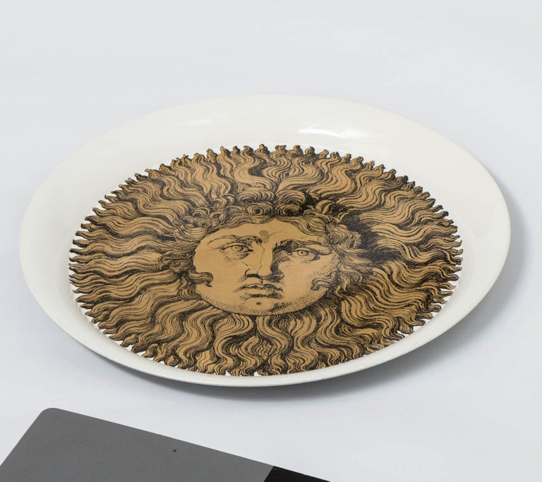 """A Piero Fornasetti tray. """"Sole"""". Lithographically printed. Hand colored and gilt highlighted on white ground. Metal. Italy, circa 1960. Measures: 39.5 cm diameter x 3 cm high."""
