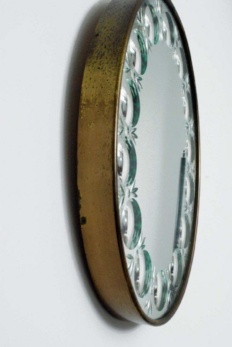 Piero Fornasetti optical mirror. Has brass trim and is oval shaped.