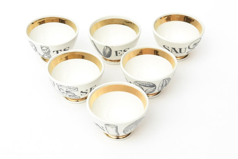 These fabulous small Mid-Century Modern Piero Fornasetti appetizer small serving bowls are porcelain with gilded gold edges, bottom and insides. They are the complete set of 6 and are clever barware and serving pieces. The bowls are labeled with