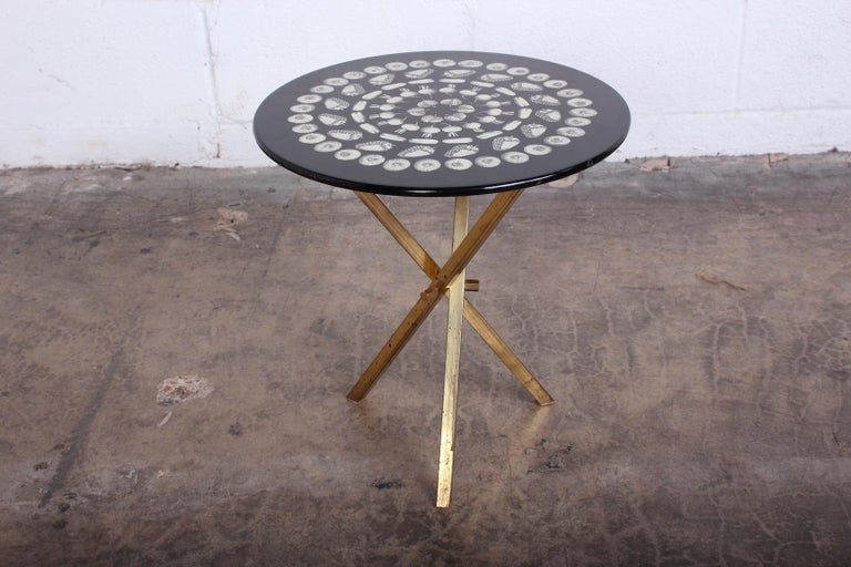 Side table with brass base designed by Piero Fornasetti, 1960s.