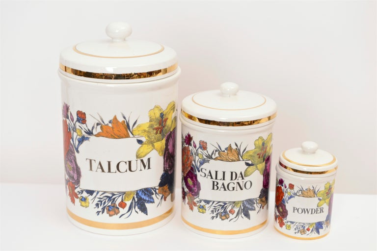A wonderful collection of three ceramic storage jars designed by Piero Fornasetti, circa 1960. These highly decorative pieces feature hand-coloured floral transfers within the glaze whilst the contents labels read… 'Talcum', 'Sali Da Bagno' and
