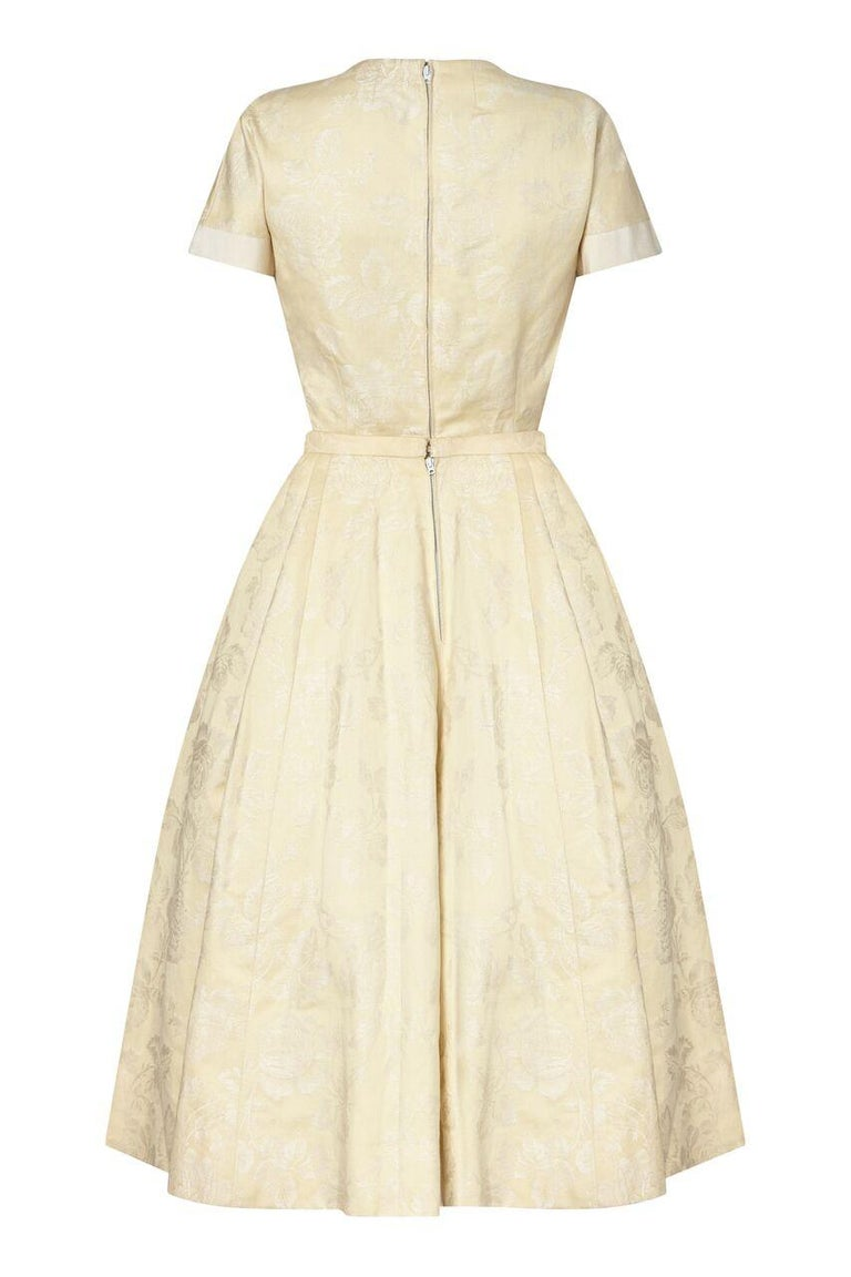 This timeless 1950s New Look style Haute Couture two piece by Pierre Balmain is in impeccable condition with exceptional line and form. The soft cream jacquard fabric is embossed with a romantic rose design and features wide bands of ivory grosgrain