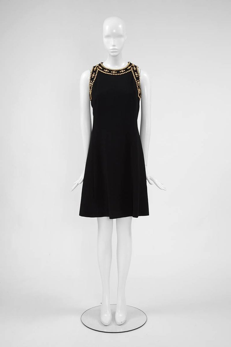 So easy to wear ! This great late 60's - early 70's Balmain Boutique dress is cut from refined black crepe and embellished with round gold metal studs around the shoulders and neckline. This sleeveless dress is ultra flattering and very chic for any