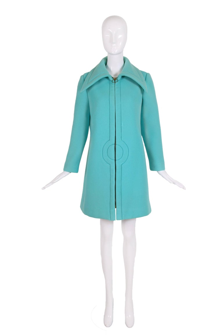 Late 1960's/early 1970's Pierre Cardin aqua blue melton wool coat with oversized collar and classic Cardin stitched circle design motif at center front near waist. Oversized metal zipper closure at center front with oversized circular metal zipper