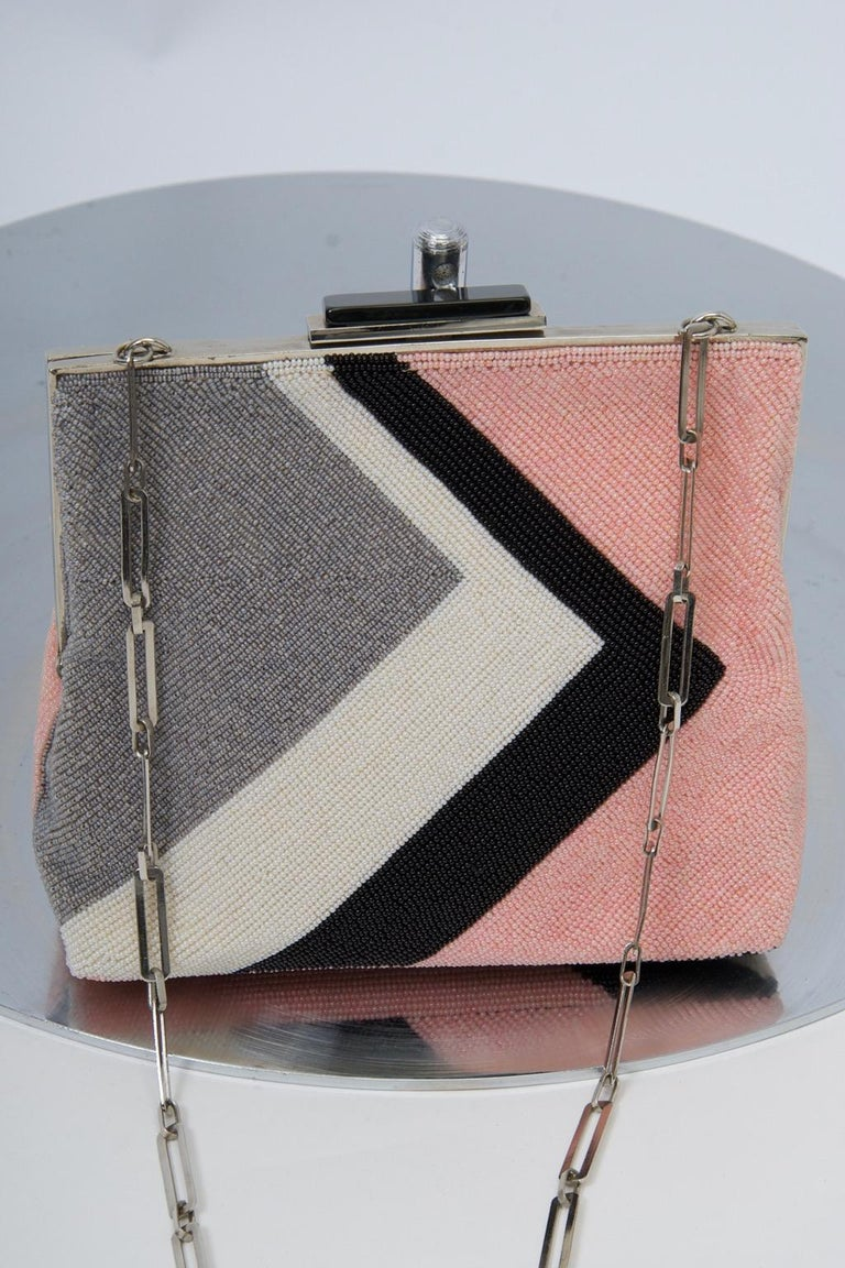 Pierre Cardin produced a line of beaded bags duirng his prime years that featured his favored geometric motifs and are highly collectible. This example, crafted of pink, gray, white and black micro beads, highlights a sideways V orientation, with