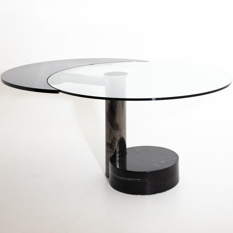 Round dining table by Pierre Cardin with revolving tabletop in black as an extendable element that changes the tabletop's shape from round to oval. The table stands on a cylindrical stainless-steel base with a black round artificial stone base.