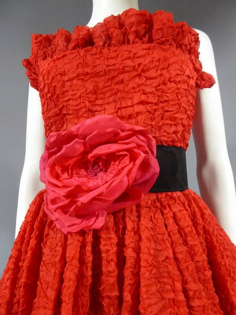 Circa 1980  France  Pierre Cardin Haute Couture strapless cocktail dress in red bubbled silk. Skirt of the short dress on the front of the long dress on the back. Borders of the skirt and bustier in the same and flying. Marked size. Red silk lining.