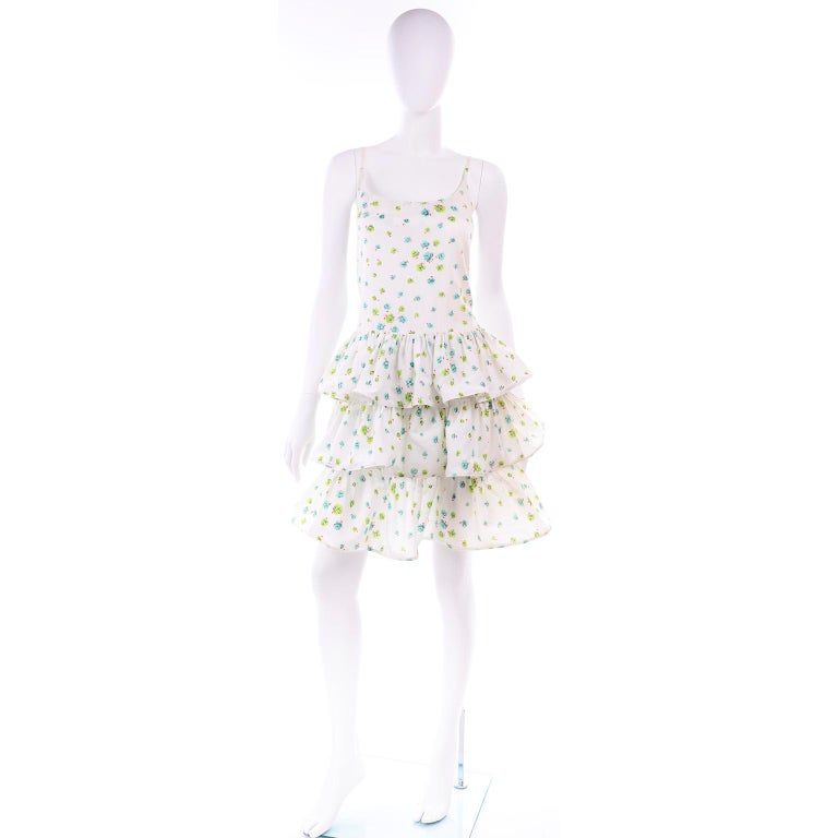 This is a very pretty vintage Pierre Cardin drop waist summer dress with tiered layers of ruffles. The dress has the Pierre Boutique label and is numbered.  The fabric is a white cotton with blue and lime green roses.  The dress closes with a back