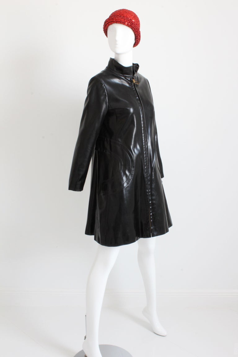 This incredible coat was made by Pierre Cardin for his Space Age and Futurism collection in 1969. Made from black vinyl, it features a mod silhouette with flared hem, a chunky zip front with brass circle pull, and circular stitching trimming the