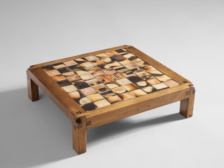 Pierre Chapo, coffee table, elmwood and glazed stoneware, France, 1960s.   Nearly square coffee table. The wooden construction show absolutely stunning wood joints, a trademark of Chapo. The top is tessellated with 64 glazed tiles, in shades of