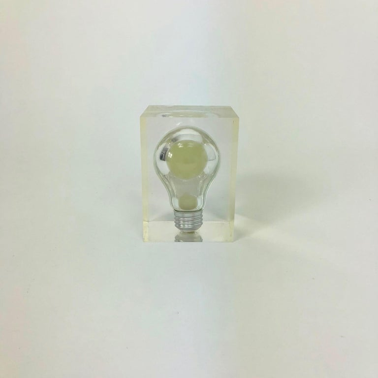 This small but amazing French Pierre Giraudon haunting pop art Lucite light bulb sculpture glows in the dark. It lights up green inside in the dark and has the appearance of a light bulb floating in mid air. The phosphorescent bulb is encased in