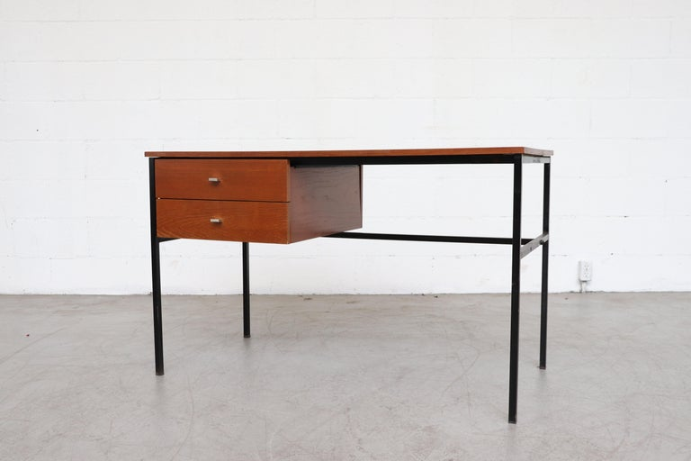 Pierre Guariche teak writing desk for Meurop with black metal frame and two drawers. Holes in frame are there to allow changing the drawer cabinet to the right side or left side. In original condition with some visual signs of wear consistent with