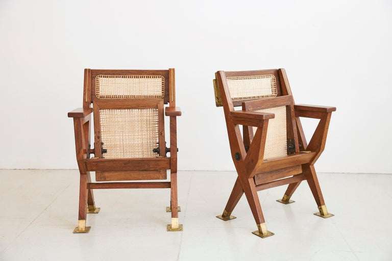 Pair of original folding Cinema chairs from Chandigarh, circa 1960 Teak wood, heavy solid brass fittings and new caning.   Measures: 34 × 23 1/4 × 19