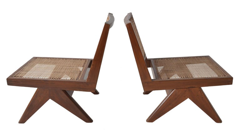 A terrific pair of rare armless low lounge chairs with caned seats by Pierre Jeanneret for the Chandigarh project. Model PJ-SI-35-A circa 1960  Solid teak construction with caned seats and backs.   These chairs have undergone a sympathetic