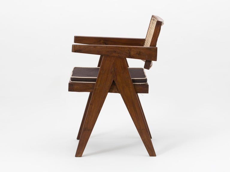 Original teak and wicker floating back armchair with cushion, designed by Pierre Jeanneret for the famous Modernist capital city of Chandigarh, India that was designed by Le Corbusier, Jeanneret and their team.   Referenced in