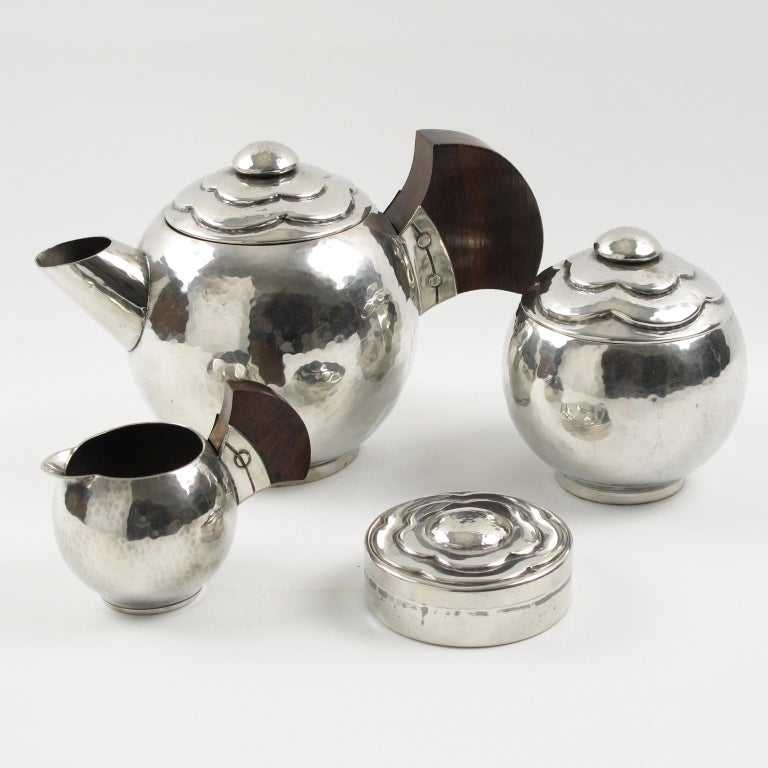 Elegant polished pewter tea or coffee set of four pieces by Pierre-Lucien DuMont, France. Set is build with coffee or tea pot, sugar pot with lid, creamer and round box. Modernist rounded shape with slight hammered pattern and embossed stylized