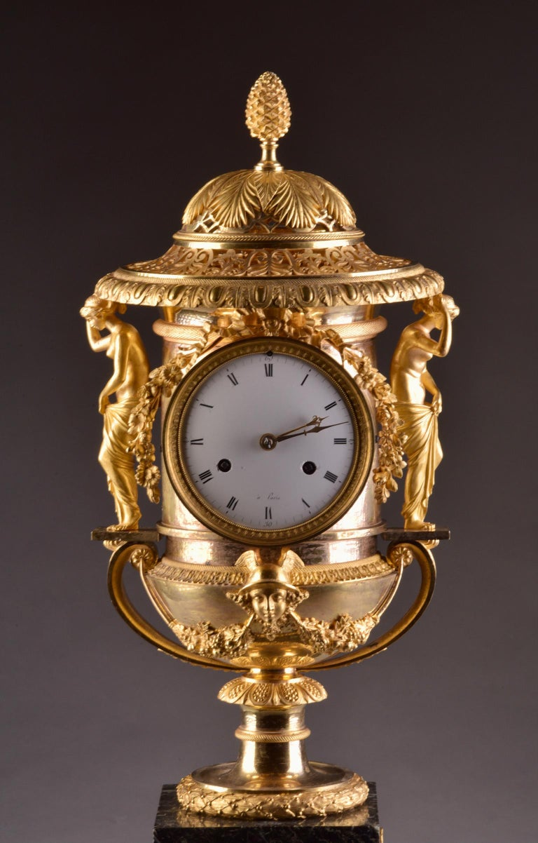 In good working order, monumental Empire 3-piece set consisting of a mantel clock and two potpourri vases, made of fire-gilt bronze on a marble base, is attributed to Pierre-Philippe Thomire (1751-1843). This clock has a vase / urn shape and the