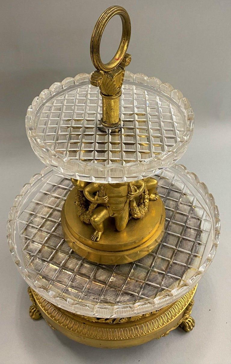 An exceptional French round centerpiece by Pierre-Phillipe Thomire (1751-1843) with tiered graduated Baccarat crystal round trays set in mercury gilt bronze with three figures holding foliate swags, supported on a round footed base with foliate and