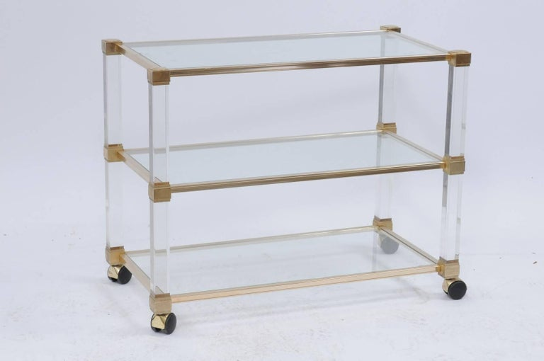 A vintage Pierre Vandel altuglas three-tier bar cart from the mid-20th century with chrome, brass and acrylic accents. We love a bar cart that doubles as a console, especially when it's a Pierre Vandel in brushed chrome, glass and brass with acrylic