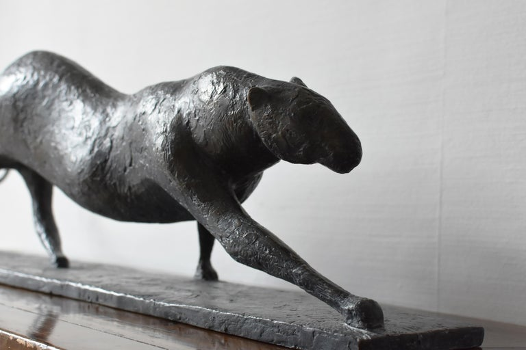 Feline IV is a bronze sculpture by French contemporary artist Pierre Yermia which represents a walking feline (a leopard, a jaguar or a cheetah). The dark patina with blue shades emphasizes the mysterious elegance of its profile.