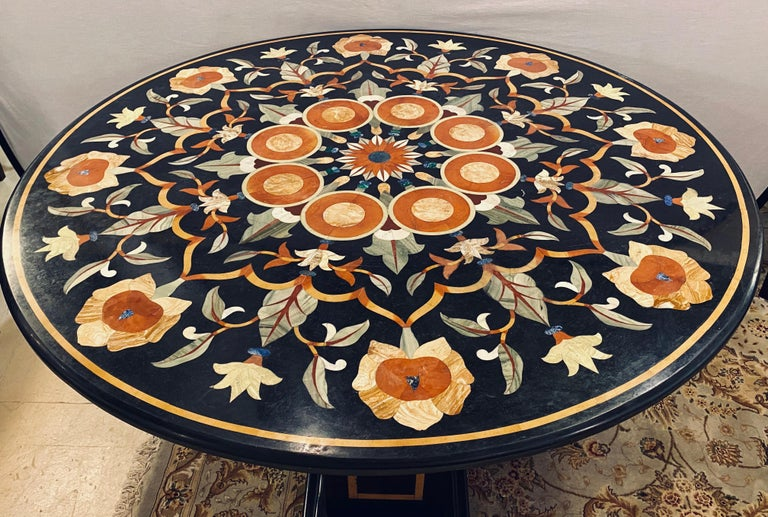 Pietradura marble top dining or center table with marble ebony inlaid pedestal base. The finely cut and inlaid marble table top is 1.5 inches thick with rounded edges and is 48 inches in diameter. This stunning center or dining table is one of two