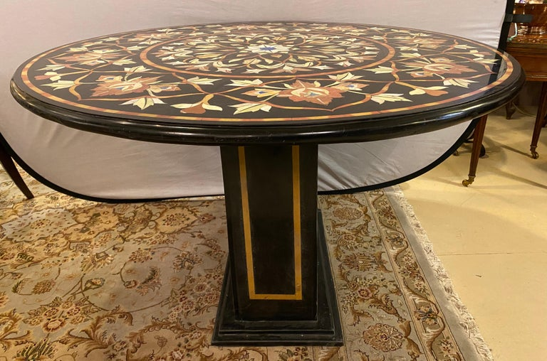 Pietra Dura marble top dining or center table with marble ebony inlaid pedestal base.The finely cut and inlaid marble tabletop is 1.5 inches thick with rounded edges and is 48 inches in diameter. This stunning center or dining table is one of two