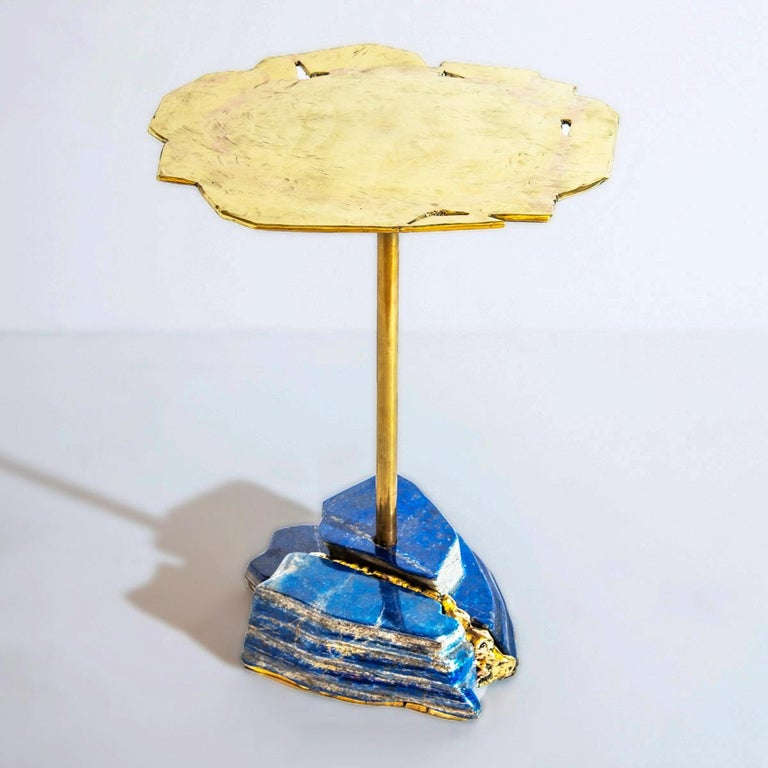 The Pietra side table is constructed on a lapis lazuli base created form several pieces of the precious stone and forged brass filling the gaps between them. The organic brass top is hand-sculpted to create an undulating effect. Base composition and