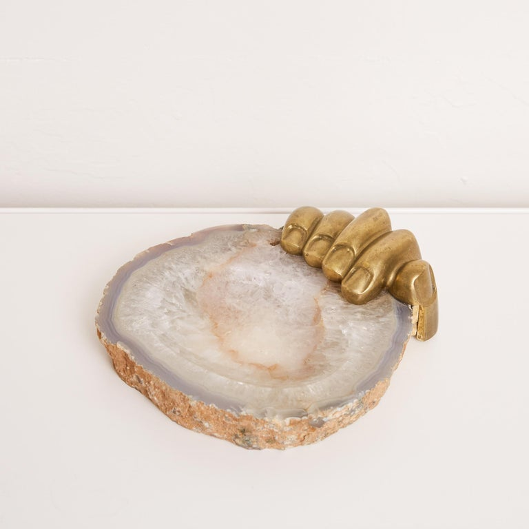 Agate tray with cast bronze hand by Italian-Brazilian artist Pietrina Checcacci. The hand carved stone bowl object features a patinated bronze hand attached to the side of the tray as if it is gripping it. The tray features a flat concave opening