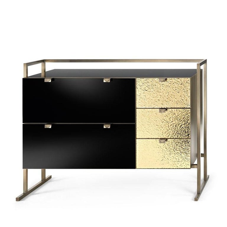 Chest of drawers Pietro with frame structure in metal in burnished and antiqued brass finish. Structure and inside drawers in matt varnished grey wood. Top and 2 drawers in black glass. 3 drawers in golden glass. Sides in metal in burnished and