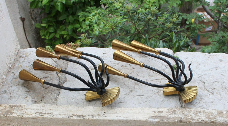 Pietro Chiesa brass candelabra sconces, with rounded socket covers and curved stems, requires five candelabra base bulbs.