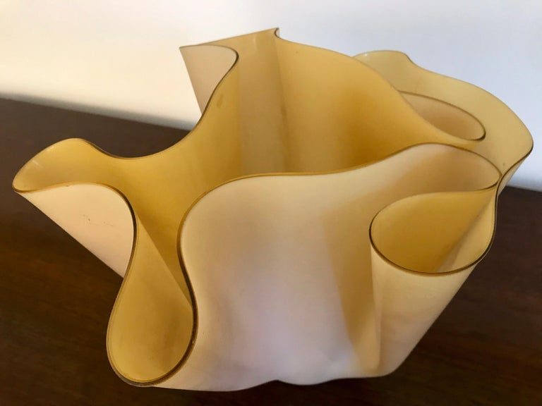 A nice folded glass form and function design. This piece appears to be an early example of its' kind. It's sort of light textured on the outside and smooth on the inside with a yellowish / butterscotch hue. Great with flowers or by itself as an