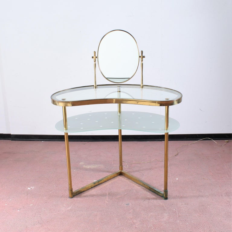 Wonderful brass and glass vanity with tilting mirror. The lighting enhances the starry motif.